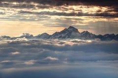 Strzępiasty śnieżny Triglav szczyt wzrasta dramatycznie nad morzem chmury Zdjęcie Stock