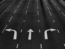 Strzałkowaci kierunki na asfaltowej drodze przy złączem w czarny i biały zdjęcie royalty free