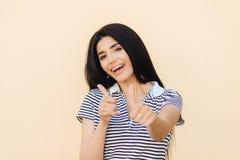 Strzał atrakcyjna Europejska kobieta daje dwoistemu kciukowi up, pozytywnego wyrażenie, białych zęby z wspornikami, ubierającymi  fotografia stock