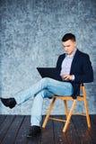 Strzał biznesmena obsiadanie na krześle i działanie na jego laptopie Zdjęcie Stock