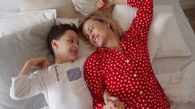 Strzał chłopiec kłaść na łóżku z jego mówieniem i matką troszkę zbiory