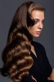 Strzał kobieta z długą glansowaną kędzierzawą fryzurą Fotografia Stock
