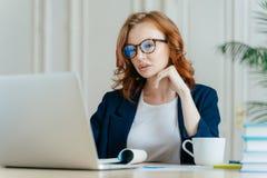 Strzał koncentrujący w monitorze laptop atttactive bizneswoman, poważnego skupiającego się spojrzenie, jest ubranym okulistycznyc fotografia royalty free