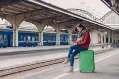 Strzał młoda Europejska kobieta ubierająca w przypadkowych ubraniach, siedzi przy bagażem, trzyma telefon komórkowego, szczęśliwe zdjęcie royalty free