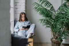 Strzał poważny skoncentrowany żeński uczeń skupiający się w podręcznika, jest ubranym pyjamas, siedzi na nadokiennym parapecie w  fotografia stock
