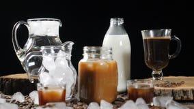 Strzał set butelki i szkła z mlekiem, wodą, czarną kawą i karmelu napojem, Sześcian lód jest spada puszkiem zbiory