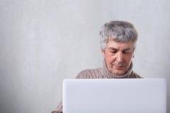 Strzał starszy męski mieć szarego włosy i wtinkles na twarzy patrzeje w ekran jego laptop czyta książkę online Han fotografia royalty free