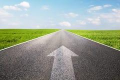 Strzała znak wskazuje naprzód na długiej pustej prostej drodze Fotografia Stock