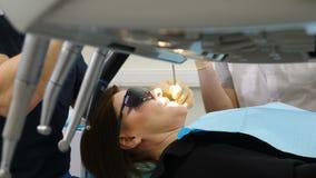 Strza? dentyst?w narz?dzia na pierwszy planu i plamy cierpliwym obsiadaniu na dentysty krze?le na tle lekarka taktuje kobiety zbiory wideo