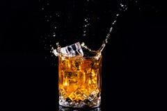 strza? whisky z plu?ni?ciem na czarnym tle, brandy w szkle obrazy stock