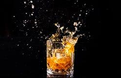 strza? whisky z plu?ni?ciem na czarnym tle, brandy w szkle zdjęcie stock