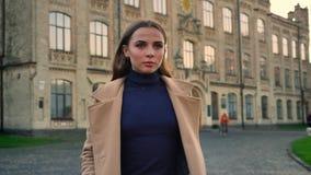 Strzelać chodząca dziewczyna patrzeje prosto naprzód z poważną spokojną twarzą w kierunku kamery, ruch ilustracja w budynkach zbiory