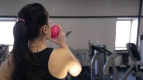 Strzelać od tylnej kobiety chodzącej wody pitnej w gym zbiory