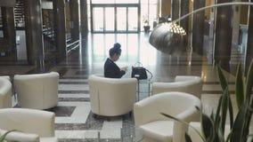 Strzelać od windy: elegancja bizneswomanu use telefonu obsiadanie w kuluarowej sala zbiory wideo