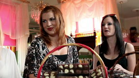 Strzelający cztery kobiety robi czekoladowym cukierkom zbiory