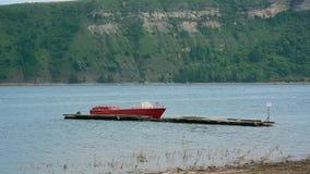 Strzelający mała czerwona łódź ratunkowa na rzece przeciw górze z lasem zbiory wideo