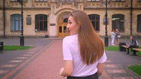 Strzelający od behind wspaniała caucasian kobieta która jest chodząca i spoglądająca przy kamerą, brać kierunek budynek