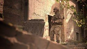 Strzelający od puszka kąta, caucasian żołnierz jest trwanie spokojny i spoglądać przy kamerą, trzyma pistolet, kamuflaż i zbiory wideo