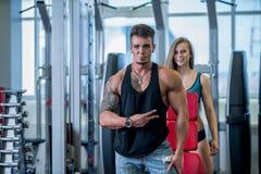 Strzelający sprawność fizyczna instruktor ono uśmiecha się w gym dziewczyna i Zdjęcie Stock