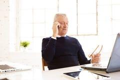 Strzelający starszego biznesmena przyglądający zamyślenie podczas gdy konsultujący z somebody na jego telefonie komórkowym fotografia royalty free