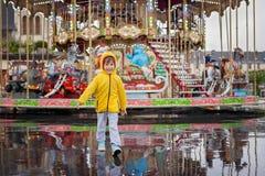 Sött barn, hållande ögonen på karusell för pojke i regnet, bärande guling r Royaltyfria Bilder