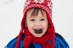 Sött litet barn, pojke som äter kakan i snövintertiden Royaltyfri Foto