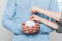 Sätta in ett mynt in i ett piggy Royaltyfri Bild
