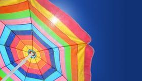 sätta på land det soliga paraplyet för dagsommaren Arkivfoto