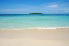Sätta på land sand med den tropiska ön på horisonten Arkivbilder