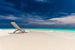 Sätta på land sikten av fantastiskt vatten och töm stol på sand för att koppla av Fotografering för Bildbyråer