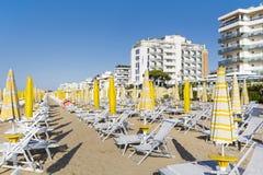 sätta på land sikten med sunbeds och slags solskydd på den vita sandiga stranden Royaltyfri Fotografi