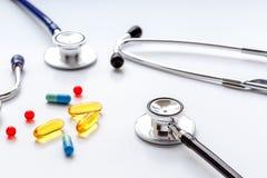 Stéthoscope sur le fond blanc avec des pilules de mélange d'isolement Image stock
