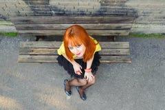 stting在凳子概略的视图的红发逗人喜爱的女孩 免版税库存照片