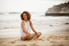 stting在海滩的年轻混杂种族妇女 库存照片