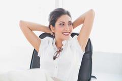 Stützende Geschäftsfrau, die an ihrem Schreibtischlächeln sitzt Stockfotos
