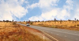 Freedom and adventure, road trip in the desert of the Outback, Australia. A car is driving at the Stuart Highway in a desolate landscape in the Australian Royalty Free Stock Images