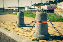 Stub posts linked in a chain on a quay Stock Image