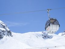 Stubai Glacier, AUSTRIA, May 2, 2019: white cable car ski lift cabin going on the top of Schaufelspitze mountain at. Stubai Gletscher ski area with snow covered royalty free stock image