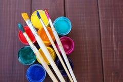 Stubarwne plastikowe puszki z farbami Artysty miejsca pracy tło Sztuk narzędzia Maluje tło Kolorowa artysta paleta Miękka część Zdjęcia Royalty Free