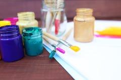 Stubarwne plastikowe puszki z farbami Artysty miejsca pracy tło Sztuk narzędzia Maluje tło Kolorowa artysta paleta Miękka część Obraz Stock