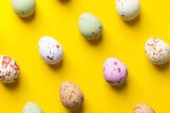 Stubarwni cętkowani czekoladowi jajka układali w isometric przekątna wzorze na jaskrawym żółtym tle Wielkanoc zdjęcie stock