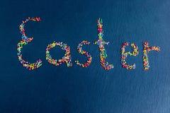 Stubarwni cukierki rozkładają w postaci wielkanocy na zmroku - błękitny tło zdjęcie stock
