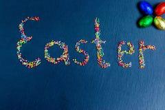 Stubarwni cukierki rozkładają w postaci wielkanocy na zmroku - błękitny tło z czekoladowymi Wielkanocnymi jajkami zdjęcie stock