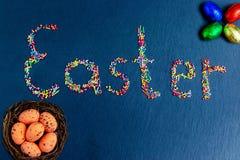 Stubarwni cukierki rozkładają w postaci wielkanocy na zmroku - błękitny tło z czekoladowymi Wielkanocnymi jajkami wewnątrz  obraz royalty free