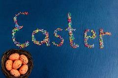 Stubarwni cukierki rozkładają w postaci wielkanocy na zmroku - błękitny tło z Wielkanocnymi jajkami w gniazdeczku obraz stock