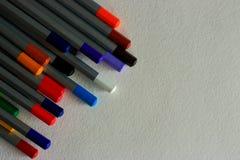 Stubarwni jaskrawi ołówki na białym textured papierowym tle Fotografia Royalty Free