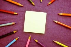 Stubarwni, jaskrawi, różnobarwni rysunkowi ołówki, lokalizują wokoło prześcieradła papier na lewicie i umieszczają dla twój tekst obraz royalty free
