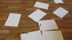 Stubarwni ołówki, pióra i markiery, opuszczają na brown podłoga którą ciąć na arkusze chaotically posypujący z białym A4 papierem zbiory