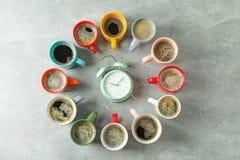 Stubarwny filiżanka kawy okrąg, budzik na popielatym tle i, odgórny widok obraz stock