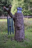 Stubbe för högväxt träd med en voljär och vindchimes arkivfoto